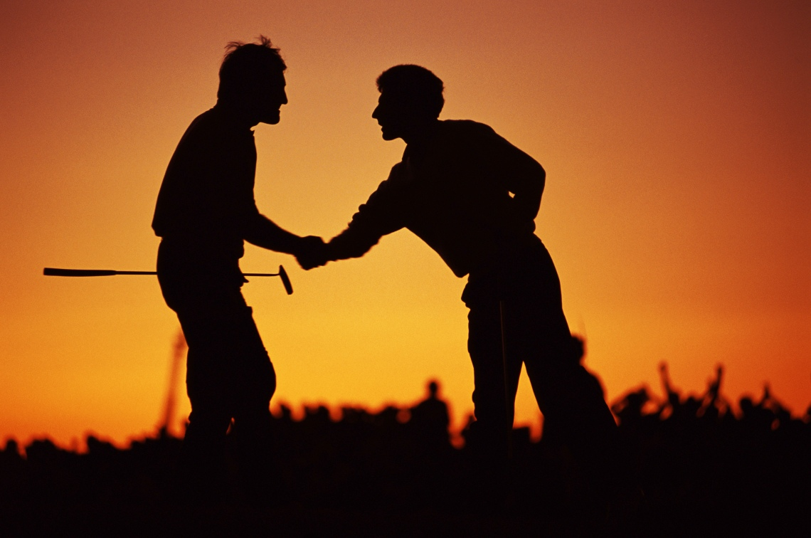 Sport. Golf. The Ryder Cup. Kiawah Island, South Carolina. September 1991. USA 14 1/2 v Europe 13 1/2. Europe's Severiano Ballesteros (left) shakes hands in celebration with partner Jose Maria Olazabal, as they are cast in shadow by the sunset.